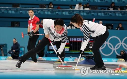 2月11日上午,在江陵冰壶中心,韩国队(白衣)在比赛中。(韩联社)