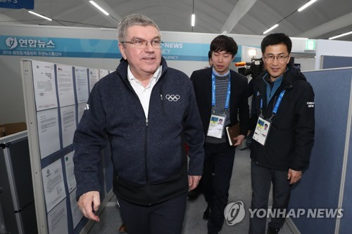 Le président du Comité international olympique (CIO) Thomas Bach visite le stand de l'agence de presse Yonhap le lundi 12 février 2018 au centre principal de presse à PyeongChang.
