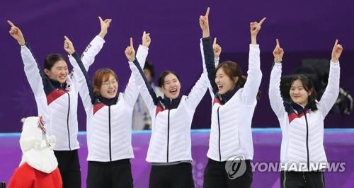 Shim Suk-hee, Choi Min-jeong, Kim Ye-jin, Kim A-lang et Lee Yu-bin (de gauche vers droite) lèvent les bras au ciel le mardi 20 février 2018 sur la plus haute marche du podium après avoir décroché la médaille d'or au relais 3.000 femmes de short-track aux Jeux olympiques d'hiver de PyeongChang, au palais des glaces de Gangneung.