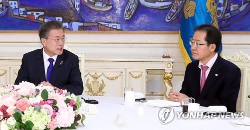 今年3月7日、青瓦台で与野党代表と会合した文大統領(左)。右は最大野党・自由韓国党の洪準杓(ホン・ジュンピョ)代表=(聯合ニュース)