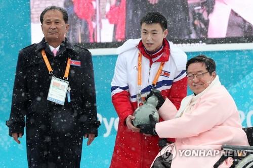 3月8日上午,在江原道平昌运动员村,出席入村仪式的朝鲜残疾人滑雪运动员金正炫(左二)向运动员村村长朴殷秀赠送纪念品,左一为朝鲜残疾人保护联盟负责人郑贤。(韩联社)