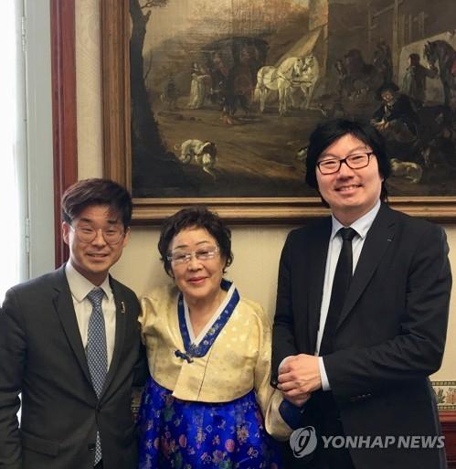 L'ancienne esclave sexuelle de l'armée japonaise Lee Yong-soo pose avec les hommes politiques français d'origine sud-coréenne Joachim Son-Forget (à gauche), député LREM (La République en marche !), et Jean-Vincent Placé, ancien secrétaire d'Etat à la Réforme de l'Etat et à la Simplification, à l'Assemblée nationale à Paris, le jeudi 8 mars 2018.