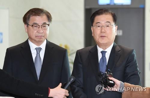 Le conseiller à la sécurité nationale Chung Eui-yong (à droite) et le directeur du Service national du renseignement Suh Hoon répondent le dimanche 11 mars 2018 à des questions de journalistes à leur arrivée à l'aéroport international d'Incheon après leur voyage aux Etats-Unis.