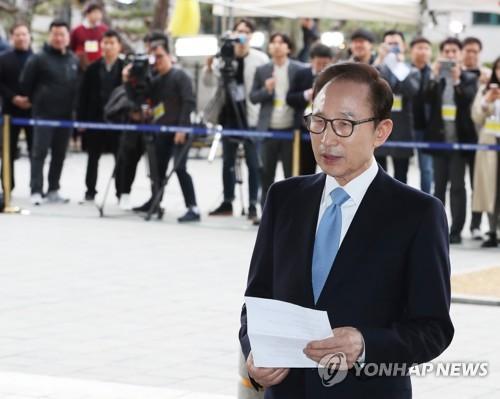 L'ancien président Lee Myung-bak lit un message le mercredi 14 mars 2018 à son arrivée au Parquet central du disctrict de Séoul pour être entendu pour une série d'irrégularités alléguées. (Joint Press Corps-Yonhap)