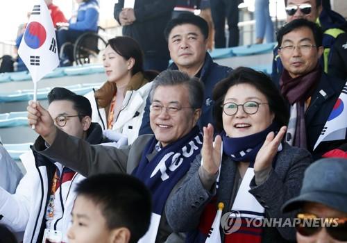 国旗を手に応援する文大統領と夫人(大統領府提供)=14日、平昌(聯合ニュース)