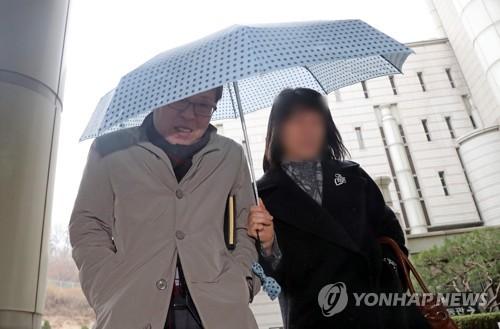 우산으로 얼굴 가리는 김문환 전 대사