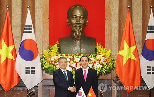 共同記者会見を終えて握手する文大統領(左)とクアン国家主席=23日、ハノイ(聯合ニュース)