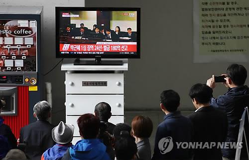 判決公判が開かれたソウル中央地裁に設置されているテレビで生中継を見る市民たち=6日、ソウル(聯合ニュース)