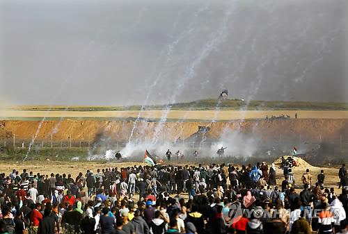 최루가스 피해 달아나는 가자지구 팔레스타인 시위대