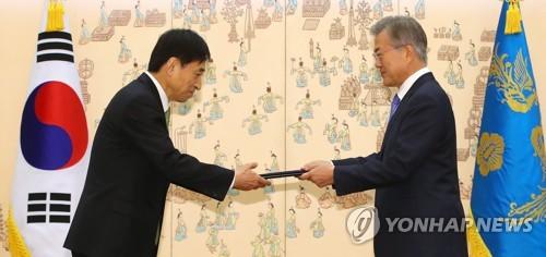 文在寅大統領から任命状を受け取る李柱烈氏(左)=9日、ソウル(聯合ニュース)