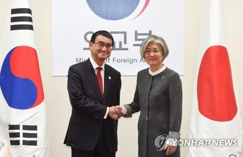 握手を交わす康長官(右)と河野外相=11日、ソウル(聯合ニュース)