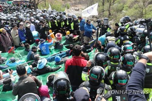 THAAD基地の入り口付近で対峙(たいじ)する警察と地元住民ら=12日、星州(聯合ニュース)