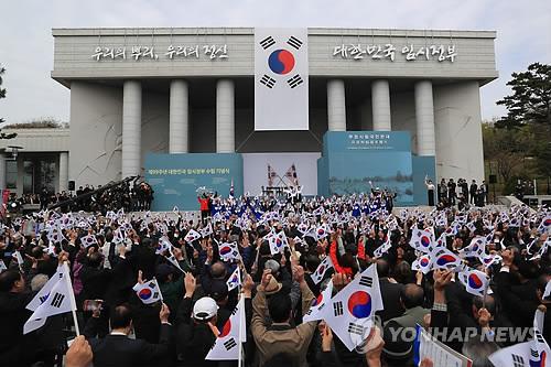 臨時政府樹立記念式で万歳三唱する出席者=13日、ソウル(聯合ニュース)