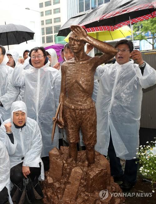釜山の日本総領事館前で、徴用工像の模型を置き集会を開く市民団体の会員たち=24日、釜山(聯合ニュース)
