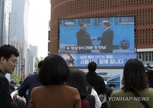 首脳会談の生中継を見つめる市民ら=27日、ソウル(聯合ニュース)