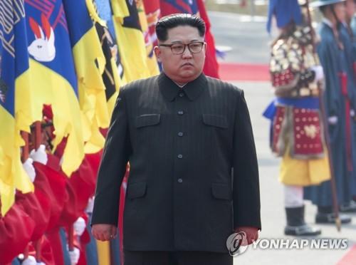 儀仗隊による歓迎行事で硬い表情を見せる金委員長=27日、板門店(聯合ニュース)