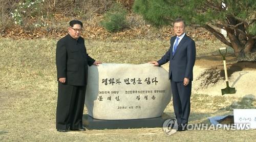 4月27日,在板门店军事分界线,文在寅(右)和金正恩在植树活动结束后合影留念。(韩联社TV提供)