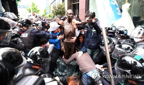 市民団体メンバーを像から引き離そうとする警察=1日、釜山(聯合ニュース)
