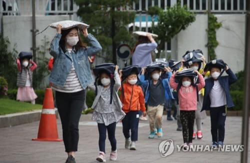 5月16日下午,在中央政府首尔办公大楼,孩子们用书包护住头撤离到户外。(韩联社)