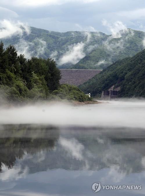 Fog rises over river