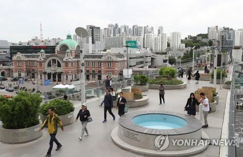 """资料图片:5月20日下午,在首尔中区,人们在改建一周年的城市中心绿地""""首尔路7017""""上悠闲散步。(韩联社)"""