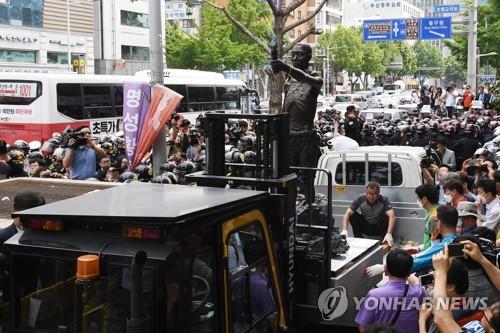 歩道から強制撤去され、トラックに積み込まれた像=31日、釜山(聯合ニュース)