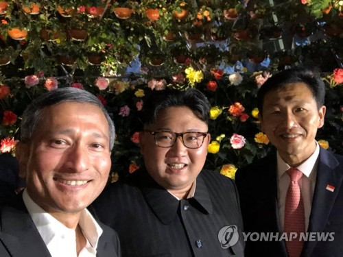 Le dirigeant nord-coréen Kim Jong-un pose pour une séance photos avec le ministre des Affaires étrangères de Singapour, Vivian Balakrishnan, le soir du 11 juin 2018, aux Gardens by the Bay, un parc situé dans le centre de Singapour. (Capture du compte Facebook de Balakrishnan)