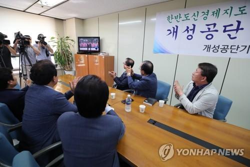 テレビで生中継される北朝鮮の金正恩(キム・ジョンウン)国務委員長(朝鮮労働党委員長)とトランプ米大統領が握手を交わす姿を見ながら拍手する開城工団企業協会の関係者=12日、ソウル(聯合ニュース)
