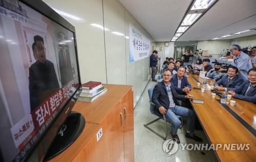 朝米首脳会談のテレビ中継を笑顔で見守る開城工団企業協会の関係者=12日、ソウル(聯合ニュース)