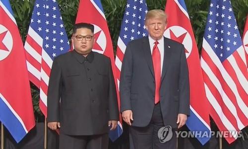 会談に先立ち記念撮影をするトランプ大統領(右)と金委員長=(聯合ニュースTV)