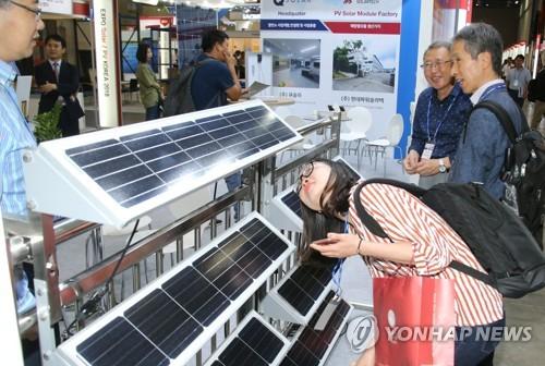 Des visiteurs devant des panneaux solaires le 14 juin 2018 au salon EXPO Solar 2018 au Centre international des expositions de Corée (KINTEX), à Goyang, dans la province du Gyeonggi.