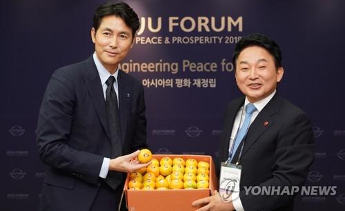 元喜龍知事(右)から済州産のミカンを贈られるチョン・ウソンさん(済州特別自治道提供)=27日、済州(聯合ニュース)