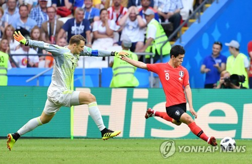 This file photo taken on June 28, 2018, shows South Korean midfielder Ju Se-jong (R) trying to pass the ball as German goalkeeper Manuel Neuer chases him during the 2018 FIFA World Cup Group F match between South Korea and Germany at Kazan Arena in Kazan, Russia. (Yonhap)