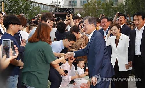 梧柳洞の幸福住宅団地を訪れ、住民と握手する文大統領=5日、ソウル(聯合ニュース)