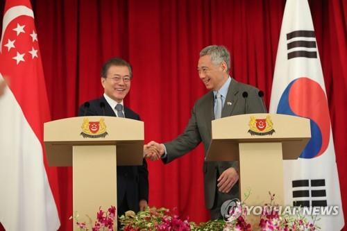 共同記者発表を終えて握手を交わす文大統領(左)とリー・シェンロン首相=12日、シンガポール(聯合ニュース)