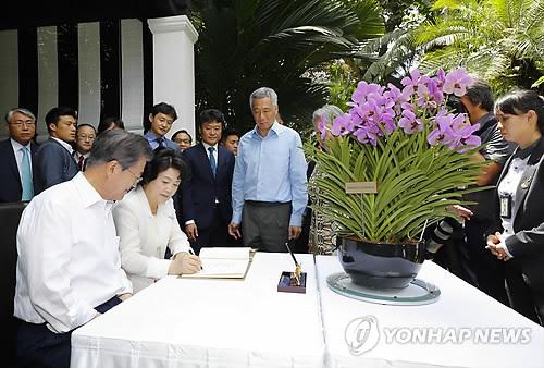 7月12日,在新加坡植物园,文在寅夫妇出席兰花命名仪式,并在留言薄上签名。(韩联社)