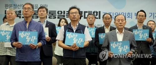 韓国労総と民主労総は7月末、サッカー大会に向け組織委員会を発足させた。「走ろう、統一へ」と書かれたカードを手にする両労組関係者ら=(聯合ニュース)