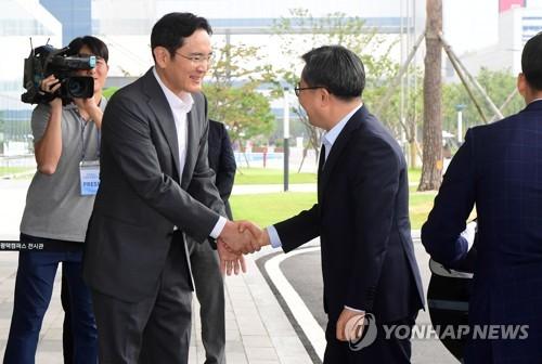 握手を交わす李在鎔氏(左)と金東ヨン氏=6日、平沢(聯合ニュース)