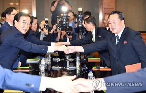 资料图片:8月13日,在板门店,韩国统一部长官赵明均(左)与朝鲜祖国和平统一委员会委员长李善权在韩朝高级别会谈上握手致意。(韩联社/联合采访团)