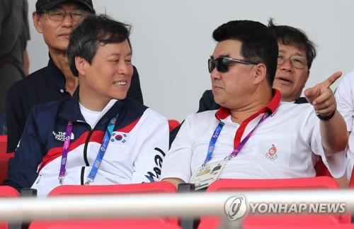 8月22日上午,在印尼巨港,都钟焕(左)与金一国同台观看亚运会韩朝赛艇联队比赛。(韩联社)