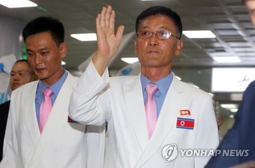 8月31日,在釜山金海国际机场,徐吉山向韩国民众挥手致意。(韩联社)