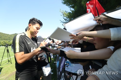In this file photo taken on Sept. 8, 2018, South Korean football player Son Heung-min (L) signs his autograph for fans at the National Football Center in Paju, north of Seoul. (Yonhap)