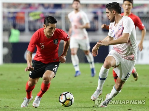 This file photo taken on Sept. 11, 2018, shows South Korean right back Lee Yong (L) dribbling against a Chile player during a friendly football match in Suwon, south of Seoul. (Yonhap)