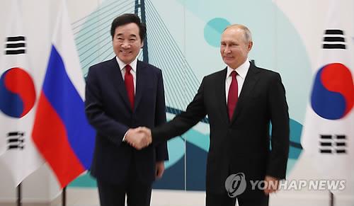 South Korean Prime Minister Lee Nak-yon (L) and Russian President Vladimir Putin shake hands during a meeting in Vladivostok on Sept. 12, 2018. (Yonhap)