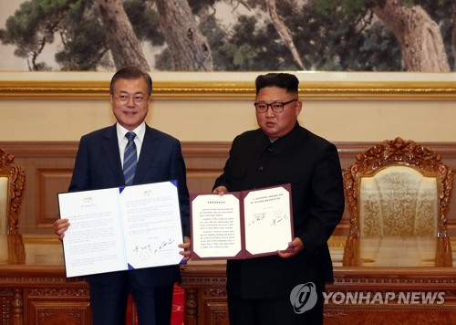 South Korean President Moon Jae-in (L) and North Korean leader Kim Jong-un pose with their summit agreement in Pyongyang on Sept. 19, 2018. (Joint Press Corps-Yonhap)