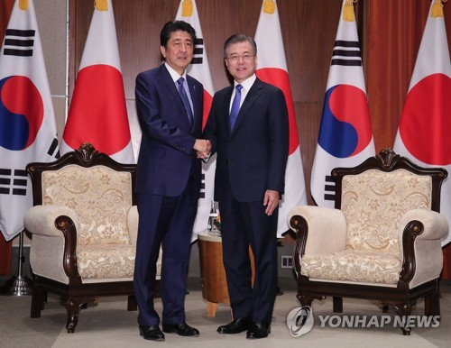 South Korean President Moon Jae-in (R) and Japanese Prime Minister Shinzo Abe shake hands before the start of a bilateral summit held in New York on Sept. 25, 2018. (Yonhap)