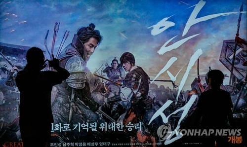 9月28日,在首尔一家影院,市民在看《安市城》海报。(韩联社)
