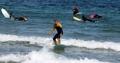 秋の海でサーフィン