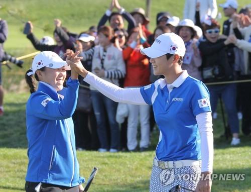 10月7日,在韩国仁川杰克・尼克劳斯高尔夫俱乐部,朴城炫(右)在第13洞成功抓小鸟后与金寅敬击掌庆祝。(韩联社/UL国际皇冠杯组委会供图)