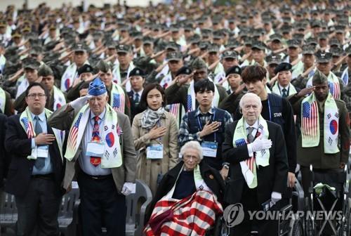 10月10日下午,第3次长津湖战役英雄追悼活动在首尔龙山战争纪念馆举行。图为参战勇士詹姆斯・伍德(前排右一)和罗伯特・佩洛(前排右三)等与会者向国旗致敬。韩联社